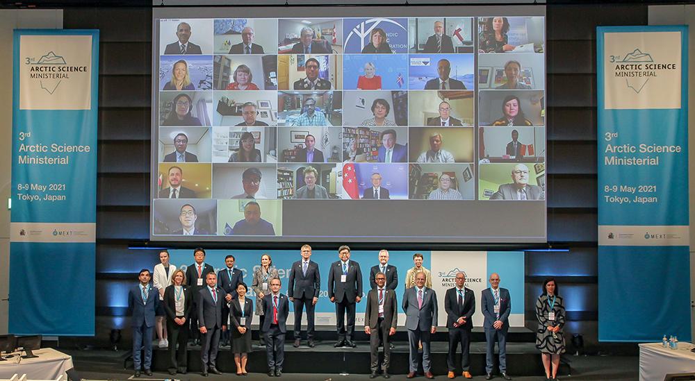 大画面に映し出されたオンライン出席の各国大臣と会場に集った各国大使の記念写真